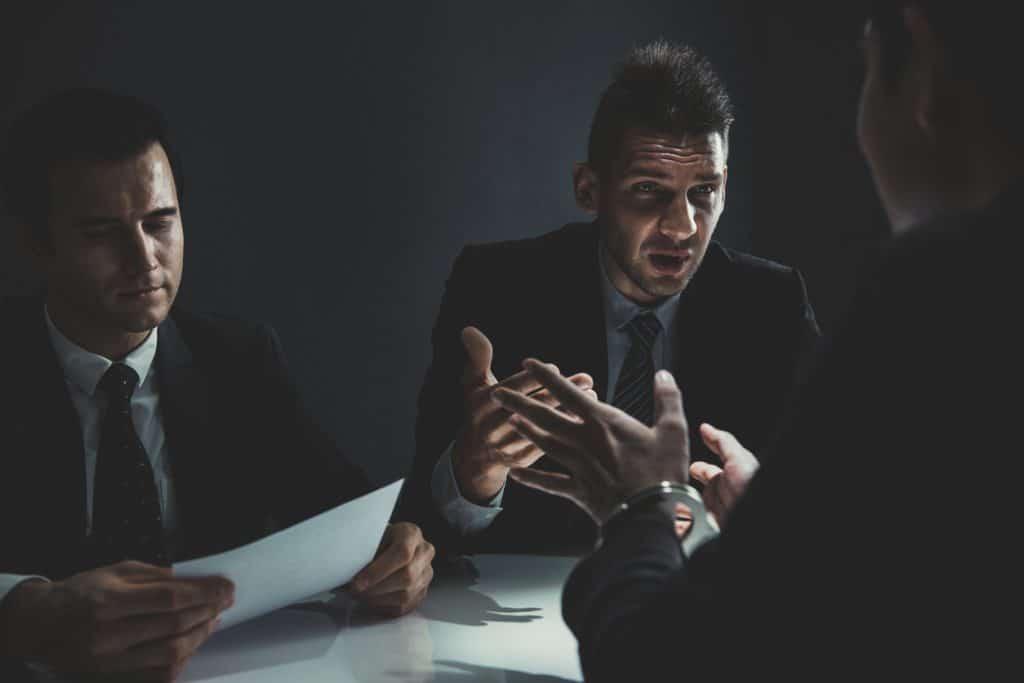 Criminal man being interviewed in interrogation