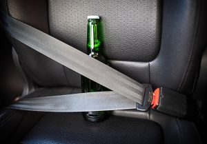 Bottle of alcohol fastened with seat belts. Drink and drive. Bottle of beer inside the car. Don't Drink for Drive.
